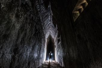 Man Holding Illuminated Flashlight While Standing In Tunnel