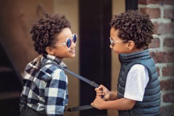 child pulling on his twin brother's suspender