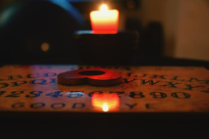 Image of a Ouija board, planchette, and a candle