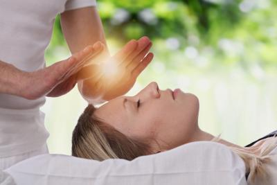 Woman having Reiki healing performed