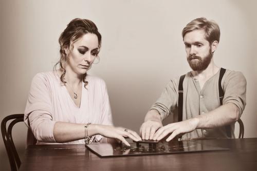 Man and woman using Ouija board