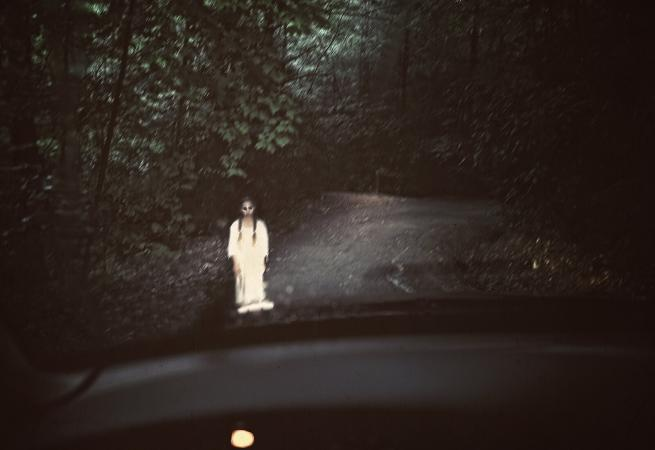 Spooky ghost standing in the middle of a dark road