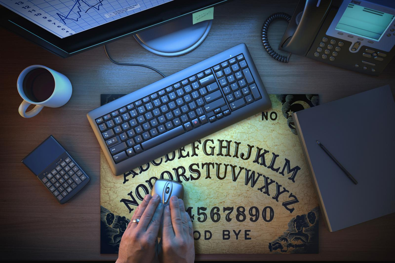Hands using computer mouse on Ouija board