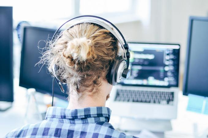 Person at computer with headphones on