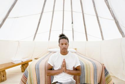 Young man meditating in teepee