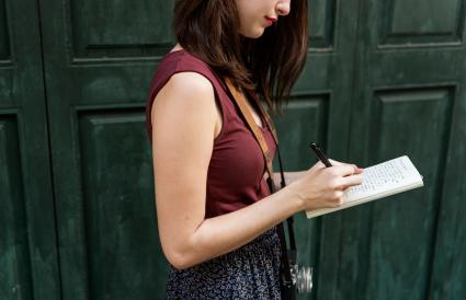 Woman Making Notes Outside City