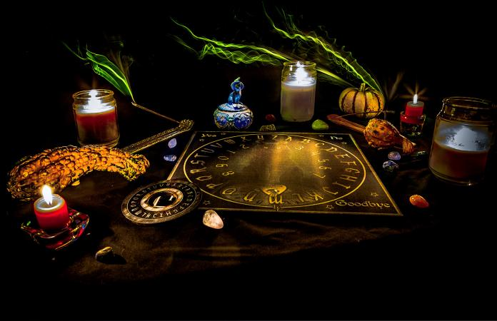 Ouija board with candles on table