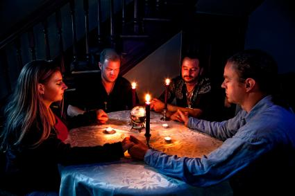 People around a table doing a séance