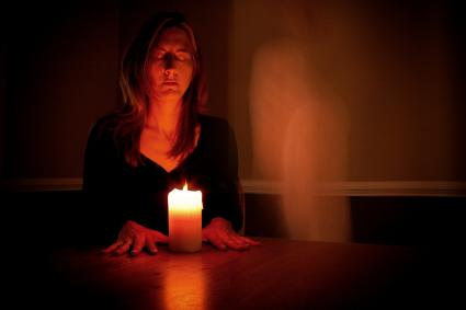 Woman calling spirits using a candle