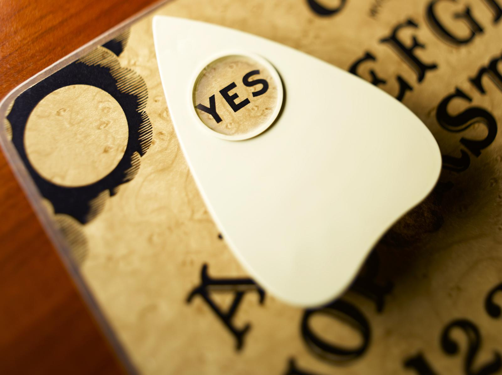 Planchette on talking board highlighting word yes