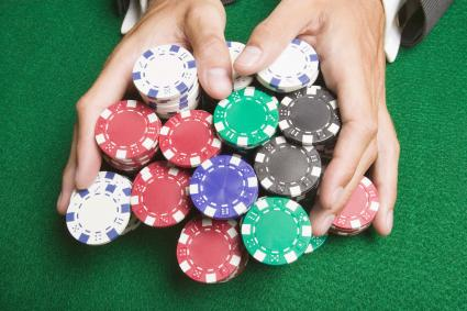 Man pushing large stack of poker chips across gaming table