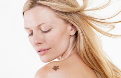 woman looking at mole on shoulder