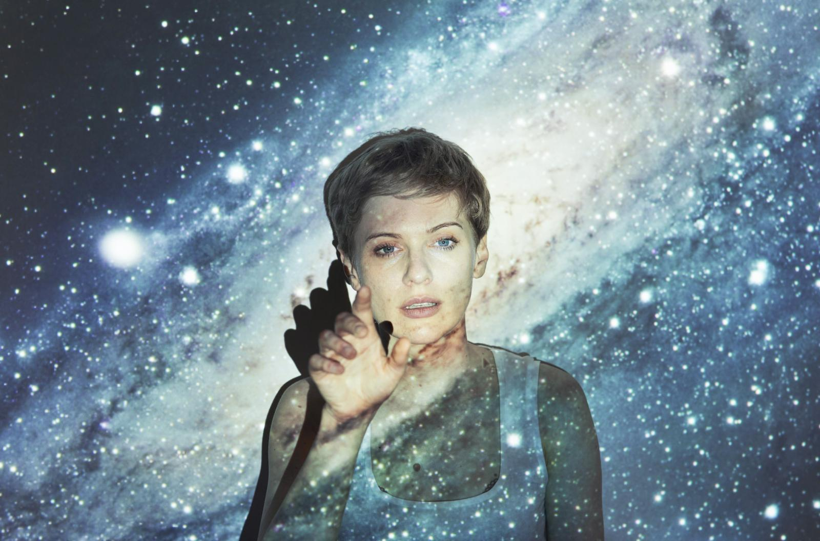 Portrait of woman with a projection of the milky way