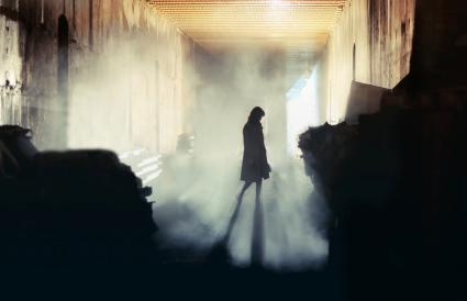 woman stands in a misty underground tunnel