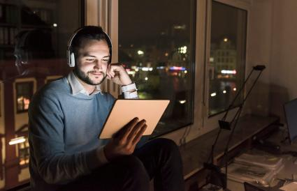 Businessman using tablet and headphones