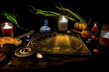 Ouija board on table with candles