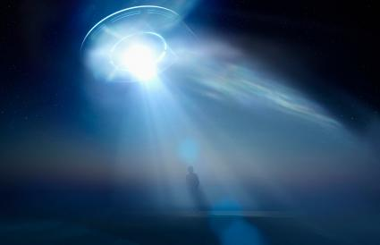Man standing in beam of light from UFO