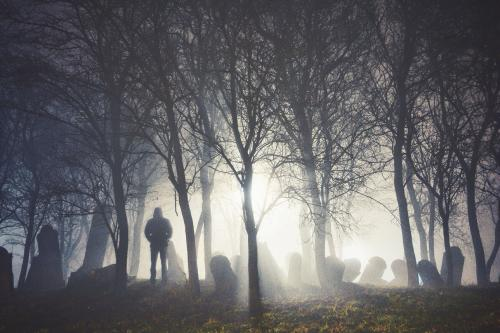man standing in a foggy graveyard
