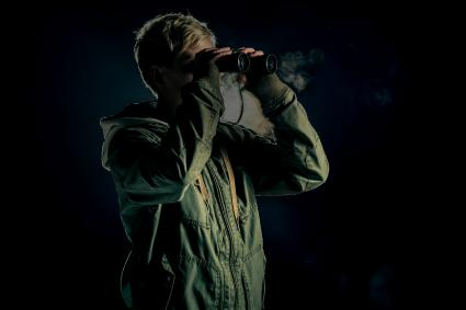 Boy looking through binoculars for orbs