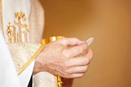 Priest holding chalice and communion wafer