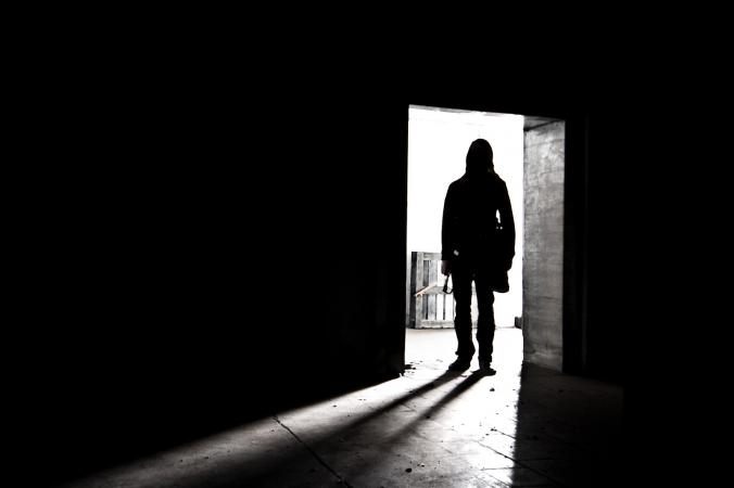 Man entering darkened room