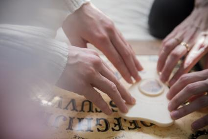 Hands on a Ouija planchette