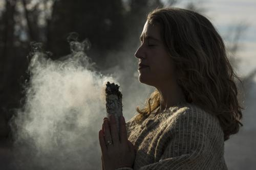 woman meditating with white sage bundle
