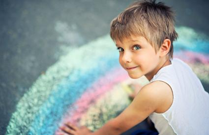 Little boy chalking rainbow