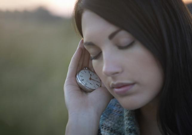 Woman holding vintage pocket watch to ear