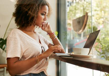 Young woman at cafe using laptop