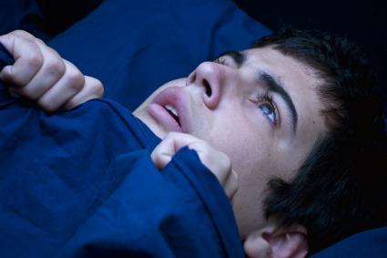 Teen boy in bed having a nightmare