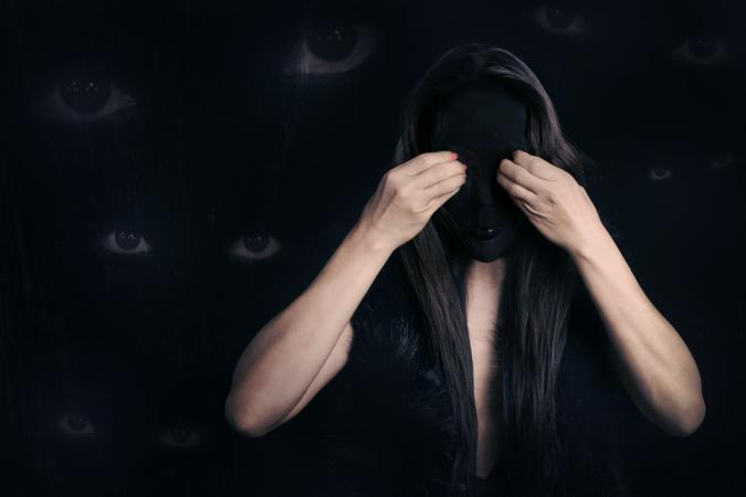 Woman wearing mask with scary eyes on background