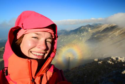 Selfie of a female hiker with broken spectre optical phenomenon shadow