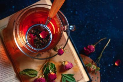 Tea strainer on an open book. Rose petals herbal tea