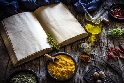 Cookbook and spices on rustic wooden table