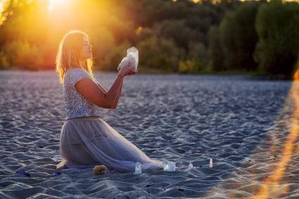 Beautiful woman on beach holding healing crystals