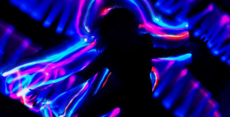 Silhouette of woman in front of illuminated neon lights