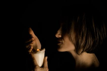 Woman in a dark room with a candle