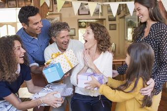 woman being given gift by family