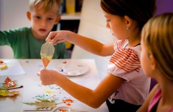 Children dipping fall leaves in paint