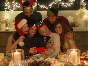 Playful friends with dog taking selfie at candlelight Christmas table