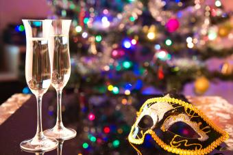 Two glasses of champagne and a black carnival mask