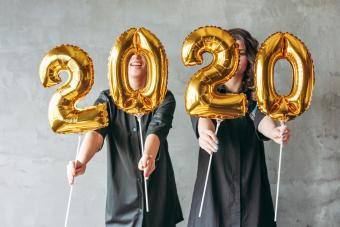 Women Holding Number Shaped Helium Balloons In New Year Party