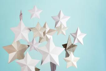 Handmade paper star decorations hanging in front of a blue green background