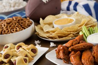 SuperBowl buffet with hot wings, pig in a blanket, nachos, pretzels, and popcorn