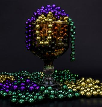 Mardi Gras beads overflowing a glass goblet