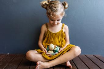 Young girl holds naturally dyed easter eggs