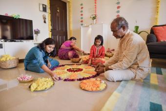 family making floral rangoli for Diwali celebration