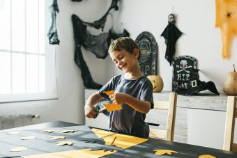 Smiling little boy cutting out for Halloween decoration at home