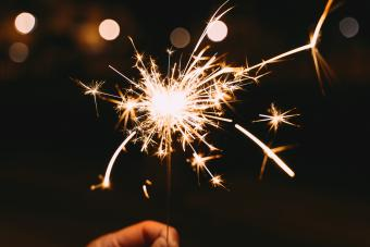 Hand holding a burning sparkler at a party